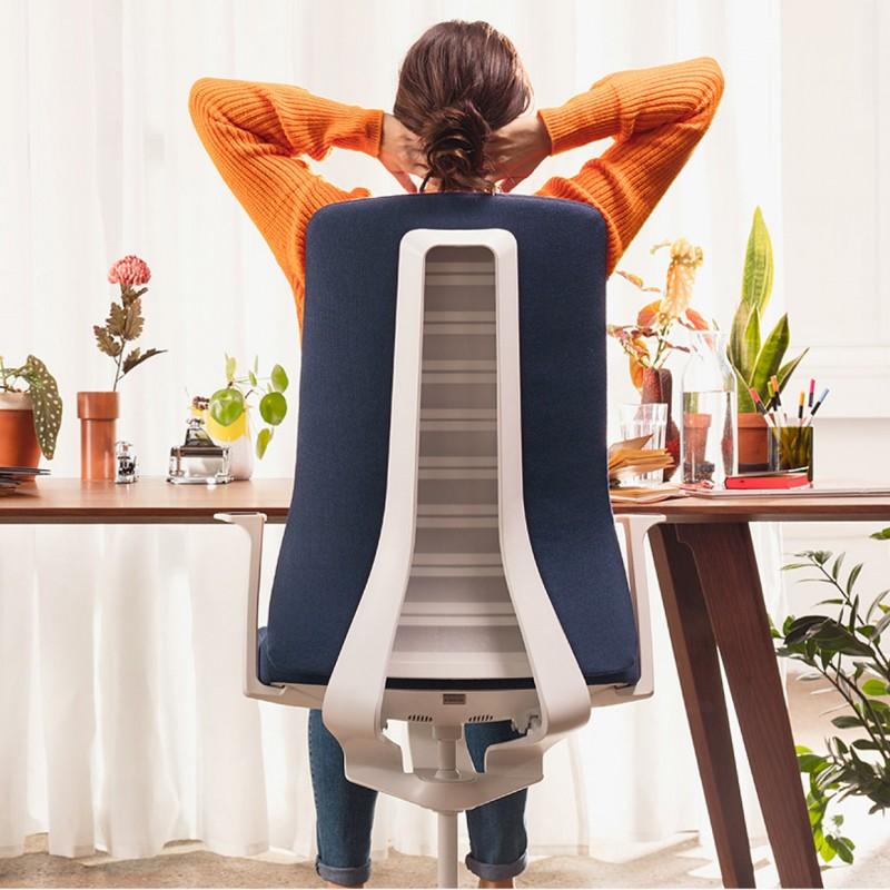 Frau sitzt auf Dreahstuhl am Tisch